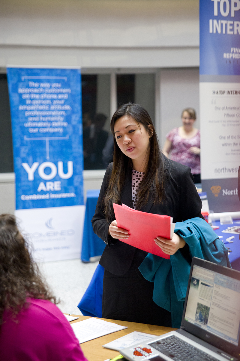 A woman with long black hair, wearing a black suit and pink dotted top stands in front of a table. She has a blue coat over her left arm and is holding a red folder in both her hands. A woman with brown curly hair, wearing a pink top, is partially visible seated behind the table. A laptop is open on the table. Some banners are partially visible in the background.