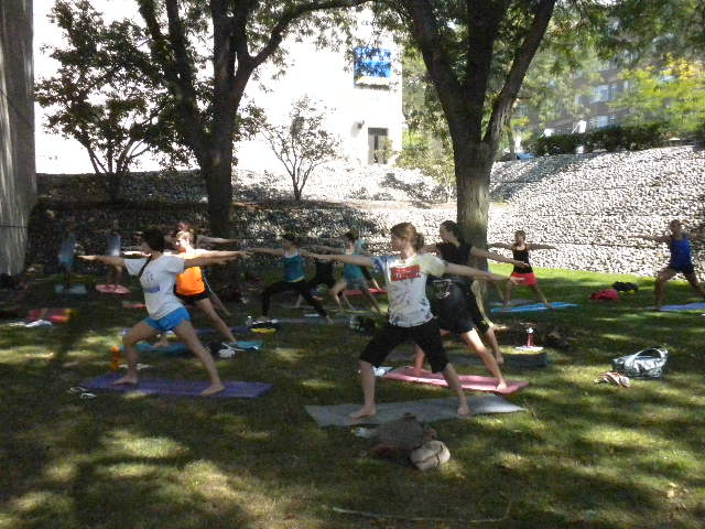 Thirteen women all stand on yoga mats with their arms stretched to the front and back and their right leg bent while their left leg is stretched out behind them. They are outside in the shade under trees.