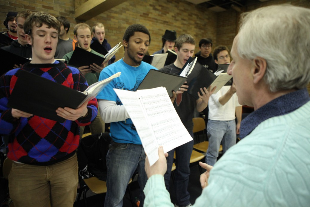A group of young men hold music and are singing. A man with white hair faces them, also holding music.