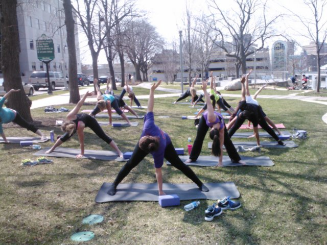 Students stand on yoga mats in a park. They are bending over and touching their left arm to the ground with their right arm raised behind them.