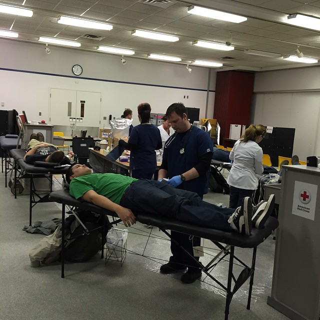A young man attends to a student who's giving blood. The student is laying on a portable bed. Other nurses and students can be seen in the background.