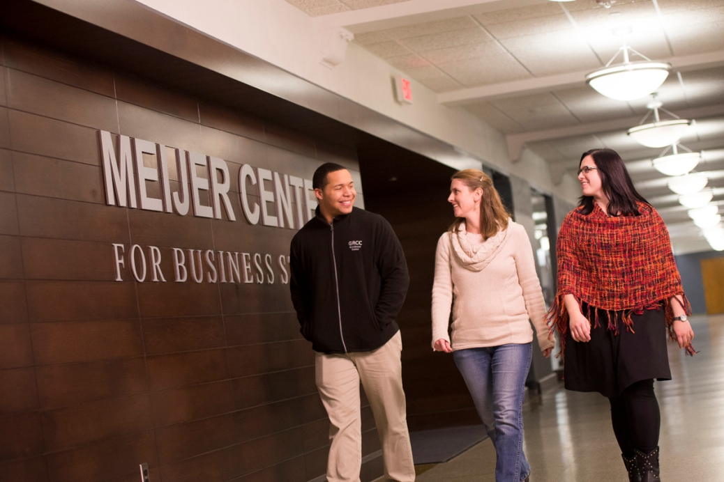 "Two young women and a young man walk down a hall. A sign on the wall says ""MEIJER CENTER FOR BUSINESS STUDIES."""