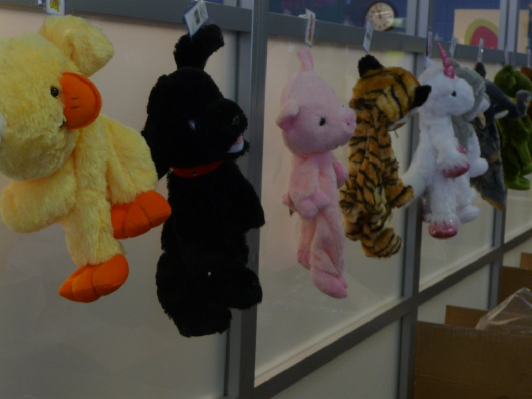 From left: a stuffed duck, a dog, a pig, a tiger and a unicorn hang from hooks on a wall.