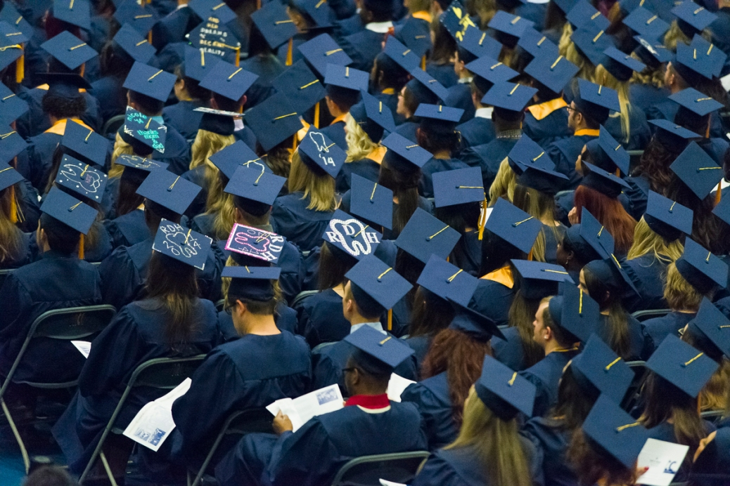 2014 GRCC graduates sit in their caps and gowns.