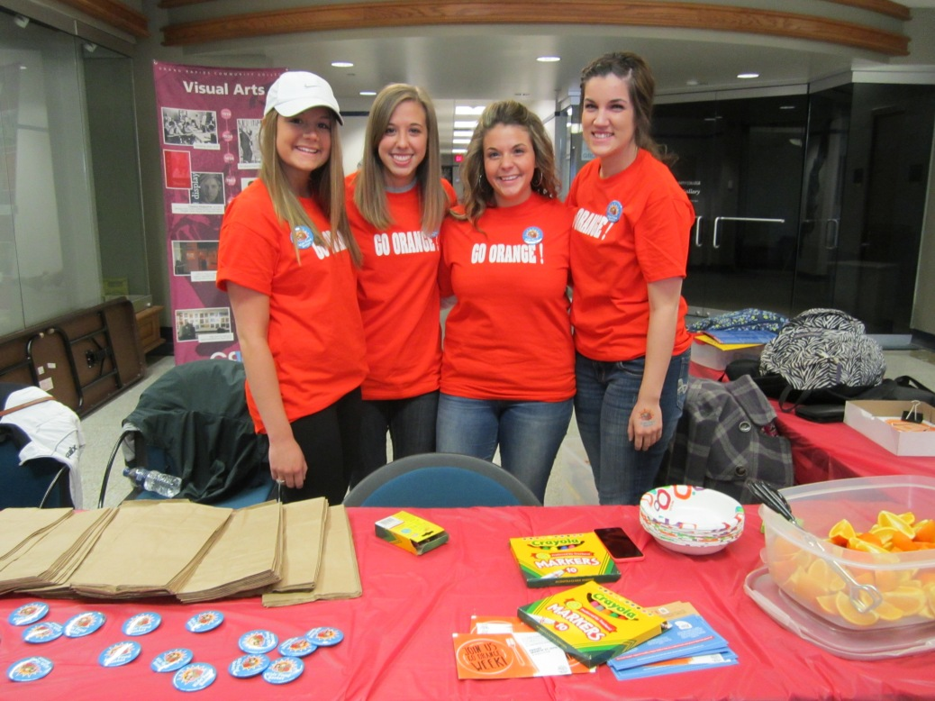"Four young women – wearing matching orange T-shirts that say ""GO ORANGE!"" on them -- stand behind two rectangular tables placed in an ""L."" The tables have stacks of brown lunch bags, markers, a plastic container of orange segments and a stack of paper bowls."