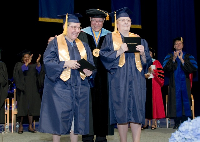 Two women in graduation caps and gowns holds up diploma cases. A man, also in a graduation cap and gown, has his hands on their shoulders. Other people, all in graduation caps and gowns, are standing behind them and applauding.