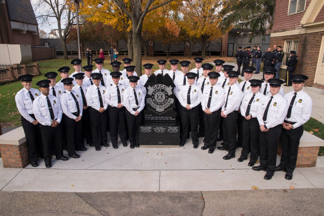 Police Academy cadets stand on either side of a memorial.