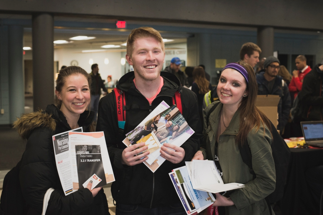 A young man and two young women show off the materials they gathered at the Transfer Event.