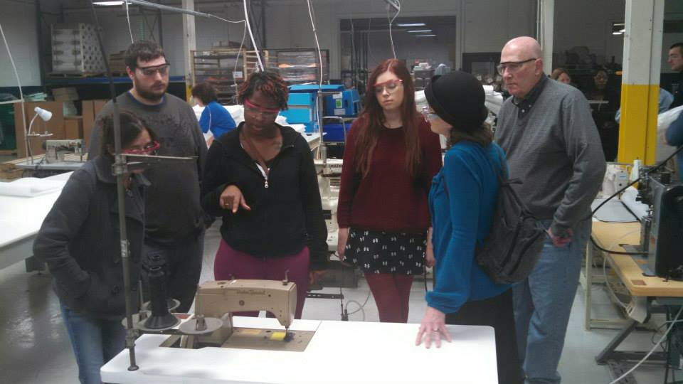 Four women and two men look at an industrial sewing machine at a work table.