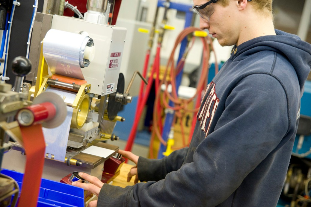 A young man in safety goggles works at a plastics machine.