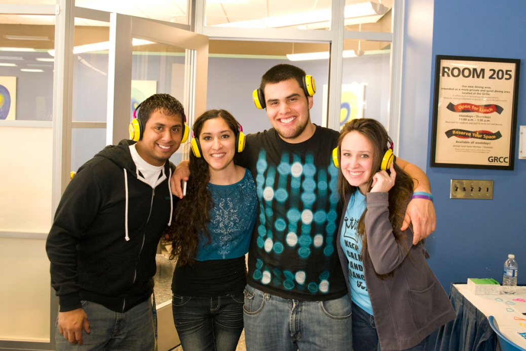 Two young men and two young women, all wearing headphones, stand with their arms over each others' shoulders in the Raider Grille.
