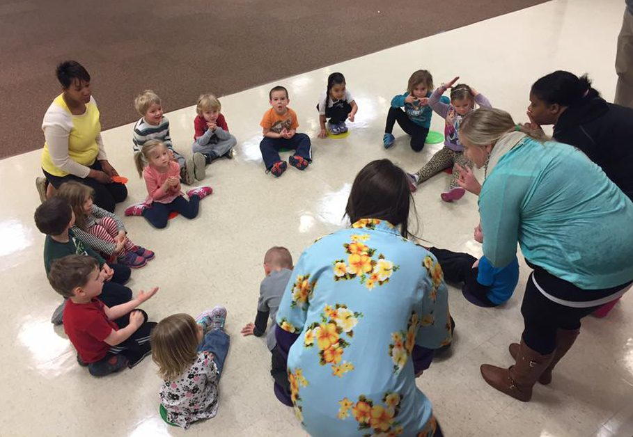 Three exercise science students talk to preschoolers who are seated in a circle.