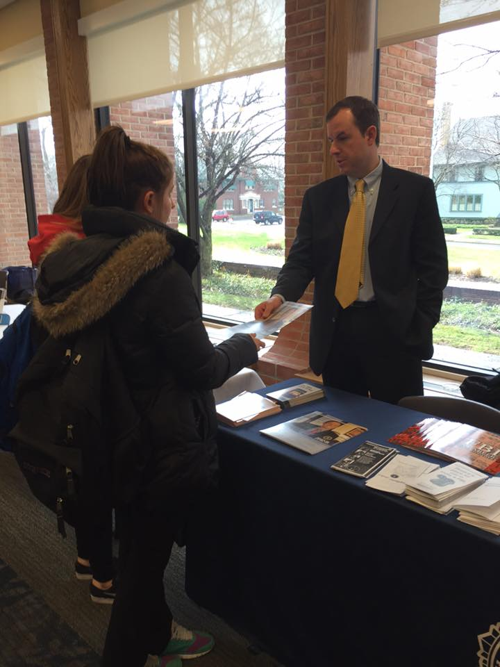 A man talks to two students at the federal career/internship fair.