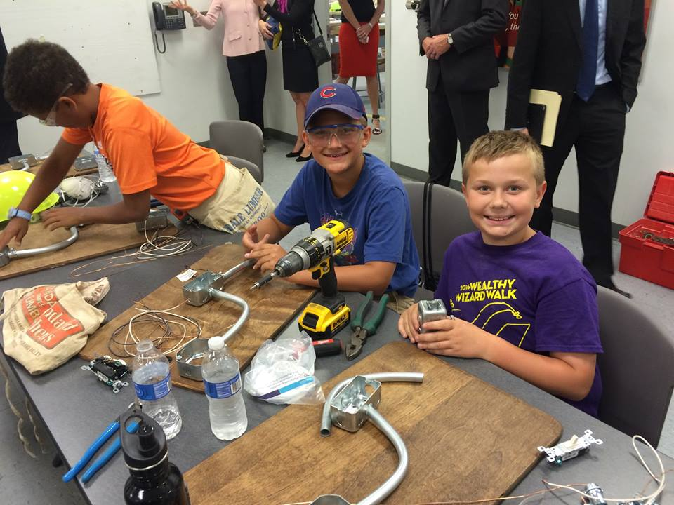 Three boys sit at a table, working on electrical wiring.