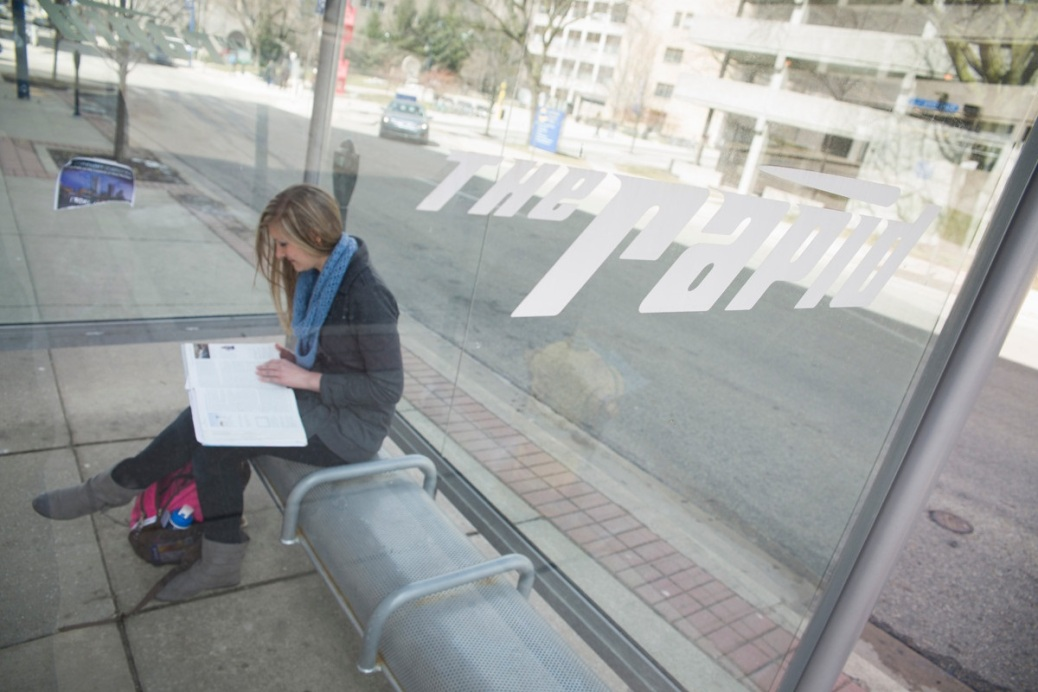 A student sits in a bus shelter.