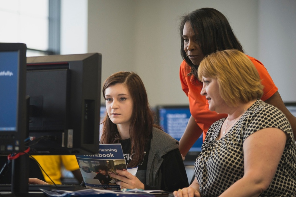 Two women and a student look at a computer in the Enrollment Center.