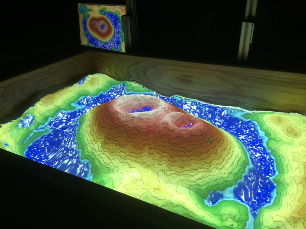 """Sand in the augmented reality sandbox has been shaped into a """"volcano"""" with virtual """"water"""" projected on it."""