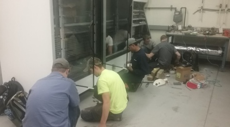 HVAC students work on installing supermarket display cases.