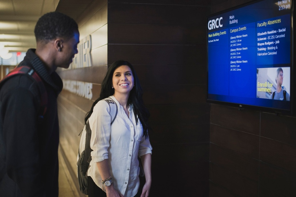Two students look at a digital sign in the Main Building