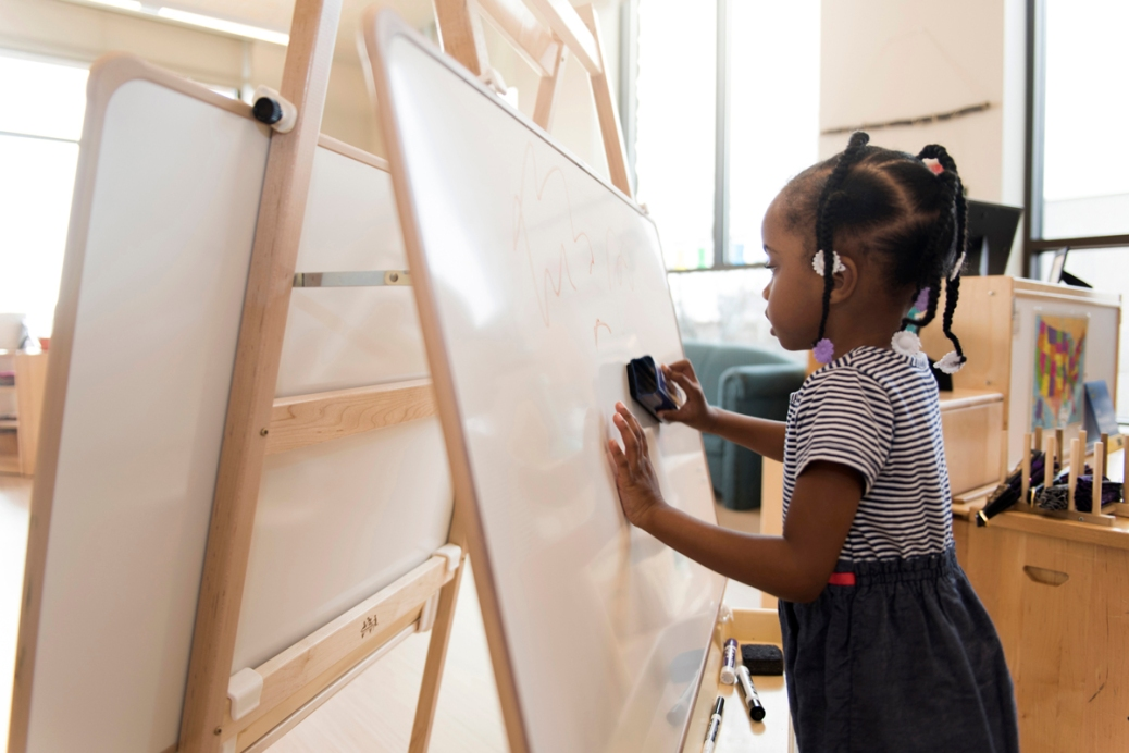 A little girl erases a whiteboard.