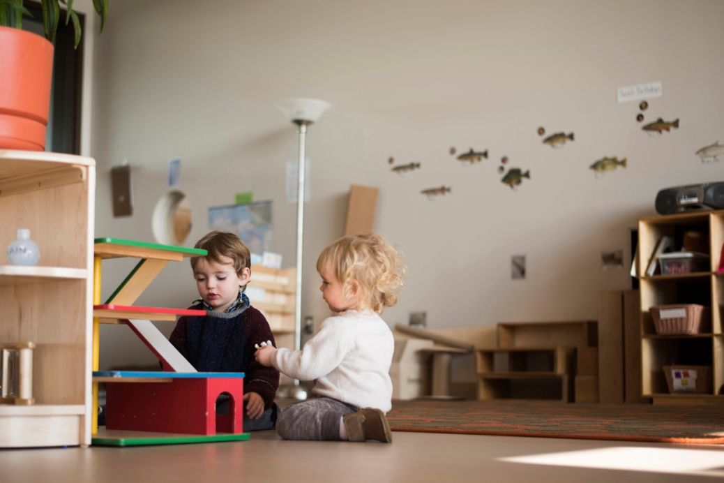 Two children sit on the floor of a preschool classroom.