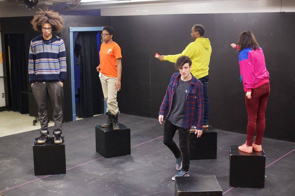 Two student actors and two student actresses stand on black boxes on a stage. Another actor walks among them.