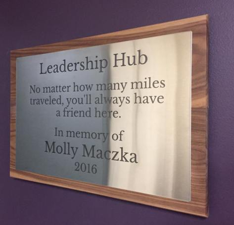 "A plaque says: ""Leadership Hub. No matter how many miles traveled, you'll always have a friend here. In memory of Molly Maczka. 2016."""