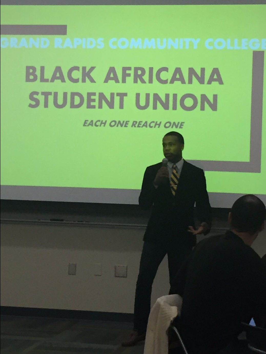 "The president of the Black Africana Student Union talks into a microphone as he stands in front of a video screen that says: ""Grand Rapids Community College. Black Africana Student Union. Each one reach one."""