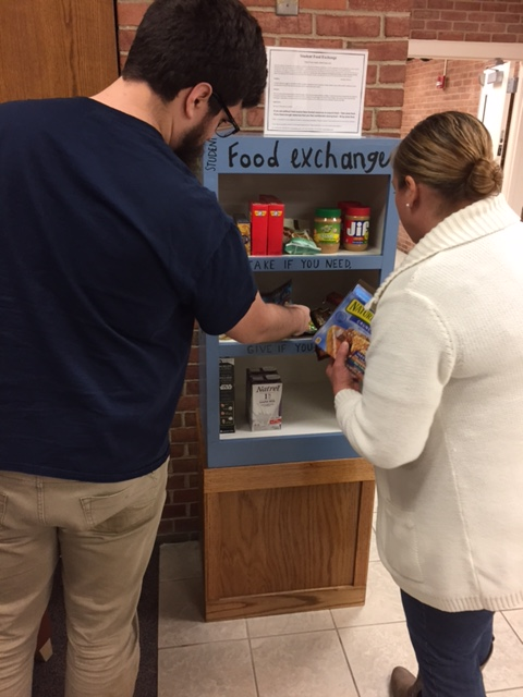 Two students place nonperishable food on the shelves of the Student Food Exchange Pantry.