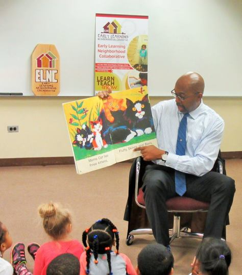 Bill Pink sits in a chair in front of children seated on the floor. He holds up a book about cats.