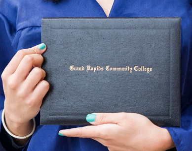 A young woman holds a GRCC degree case