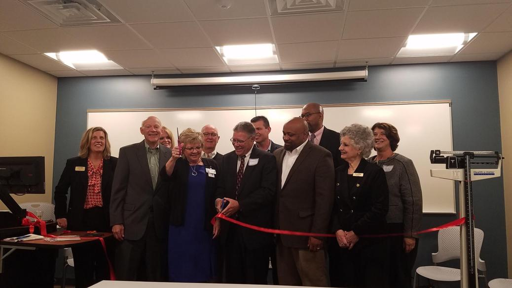 Five women and six men, including President Ender, Bill Pink, Cynthia Bristol, Julie Parks, Kenyatta L. Brame and Bert Bleke, cut the ribbon on the Certified Nursing Assistant training facility at Holland Home.