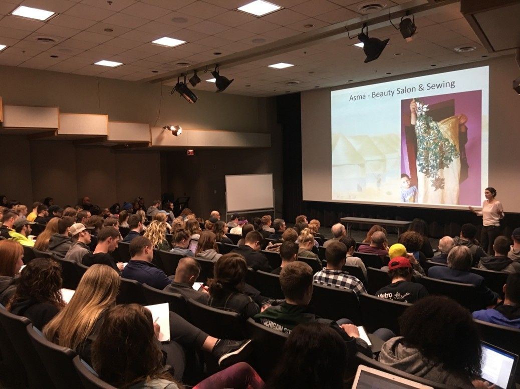 """Karen Culcasi talks to a packed ATC auditorium. On the video screen behind her, it says """"Asma -- Beauty Salon & Sewing."""""""