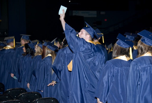 A line of GRCC graduates; one of them waves