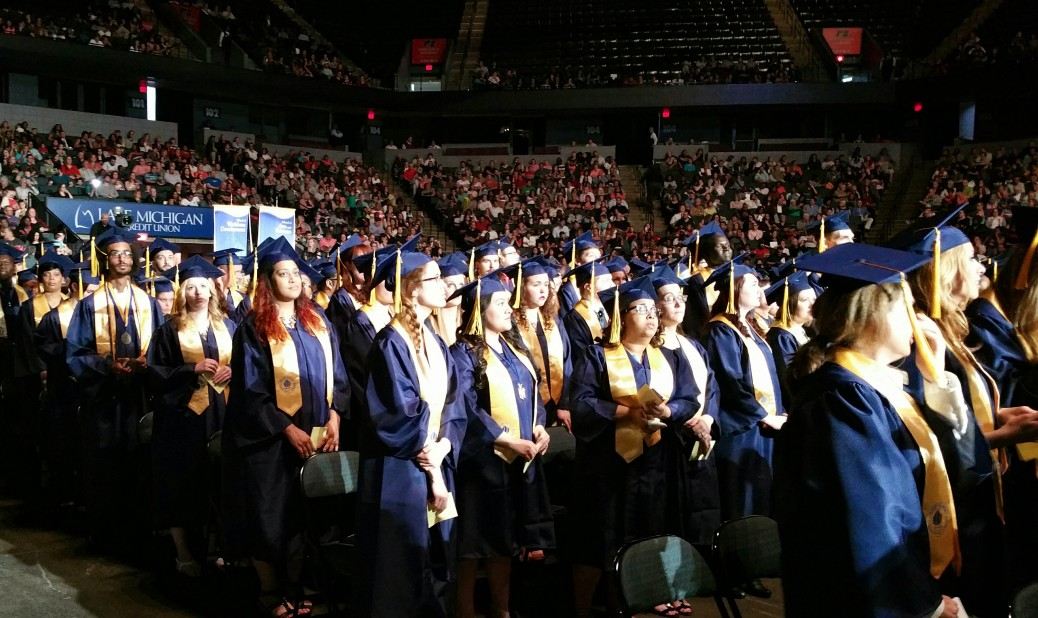 GRCC graduates stand during the ceremony