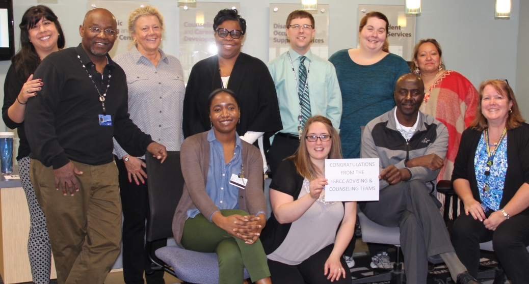 "GRCC Counseling and Career Center staff hold up a sign that says: ""Congratulations from the GRCC advising and counseling teams!"""