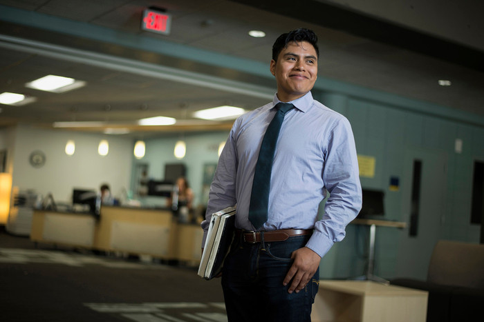 Daniel Lopez stands near the Counseling and Career Center. He holds books.
