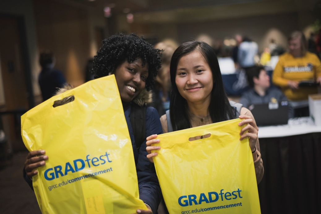 "Two students hold up bags that say ""GRADfest. Grcc.edu/commencement"""