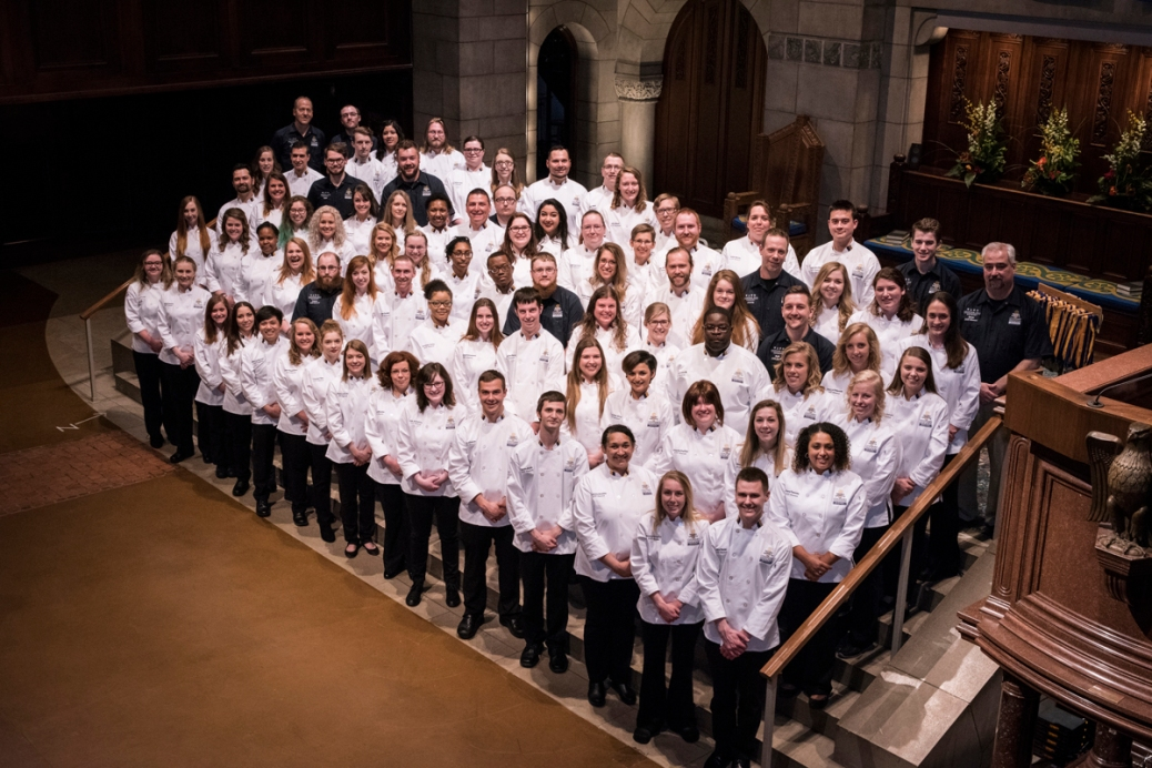 About 80 Secchia Institute for Culinary Education students stand on the inside steps of Fountain Street Church.