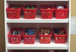 Baskets of snacks sit on a storage unit's shelves.