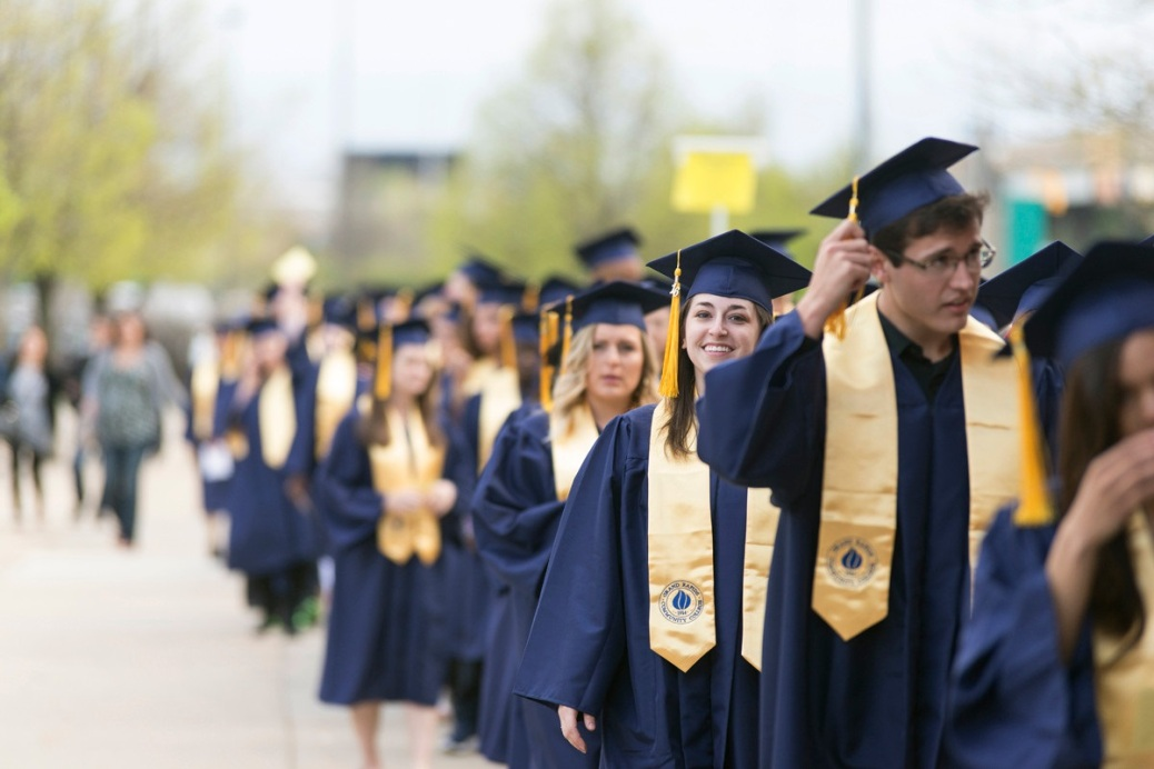 GRCC graduates stands in a line on the street.