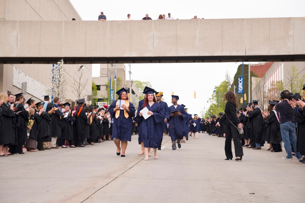 People on the walkway and along Lyons watch GRCC graduates walk down the street.