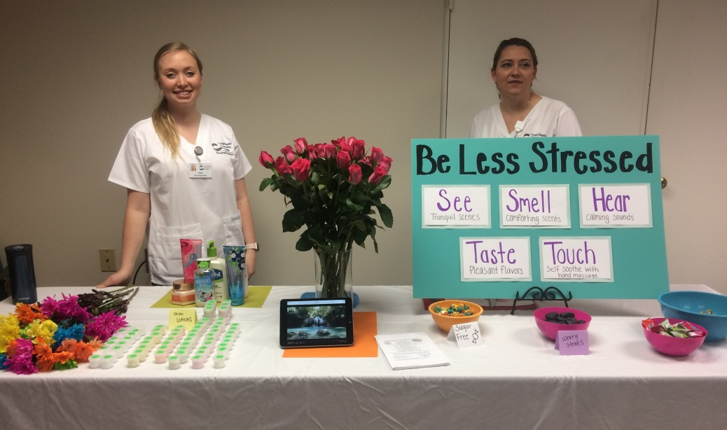 """Two students stand behind a table with a sign that says: """"Be less stressed. See tranquil scenes. Smell comforting scents. Hear calming sounds. Taste pleasant flavors. Touch with healing massage."""""""