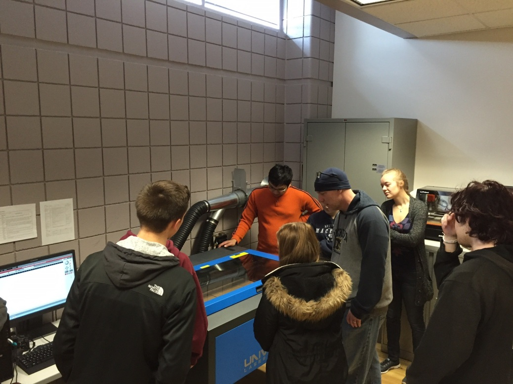 Students look at machinery in the maker lab.