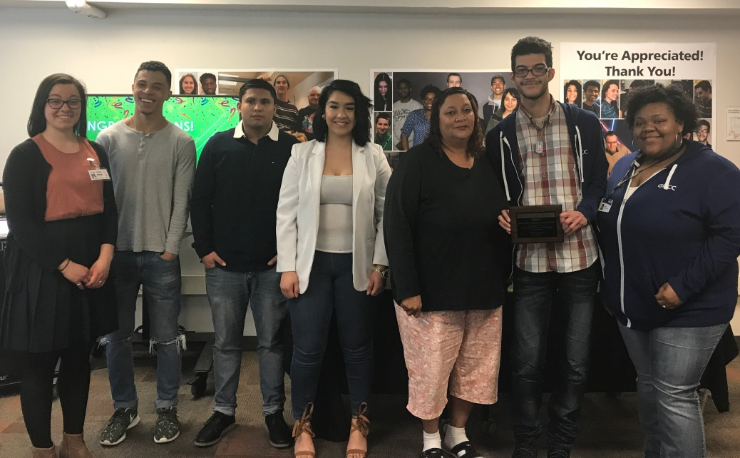 Onalee Sneller, Jamal Dawson, Jesus Lopez, Monica Rivera, Cynthia Brown, Gino Gonzalez and Imari Lamarr stand in a row. Gino holds a Student Employee of the Year plaque.
