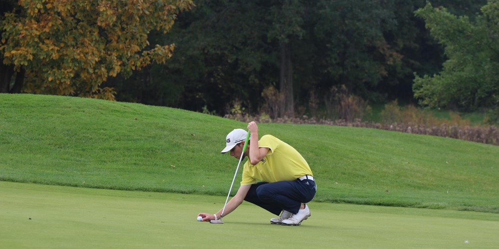 A GRCC golfer crouches near his ball on the green.
