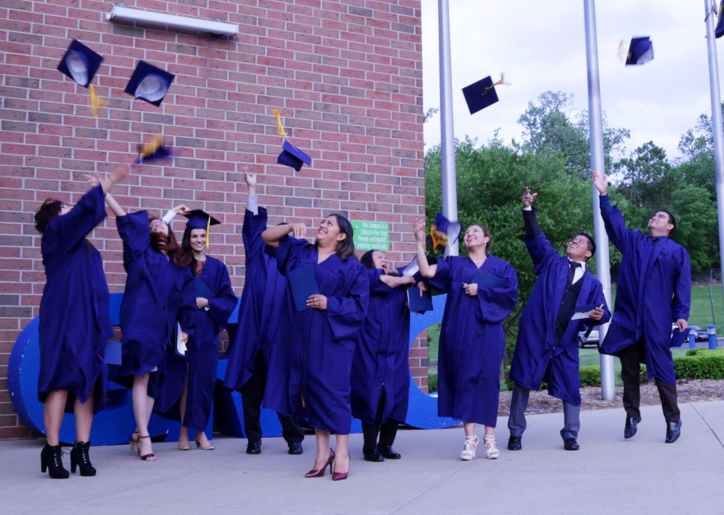 Adult Education graduates toss their caps in the air outside Tassell M-TEC.
