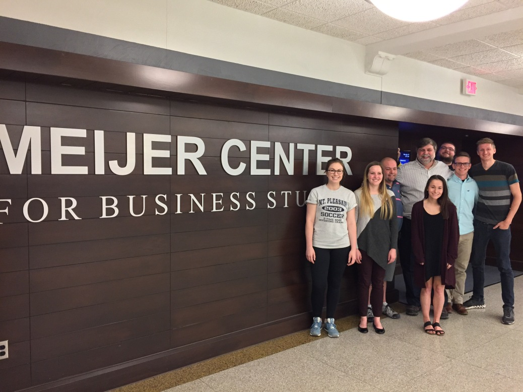Seven students stand with professor Felix Pereiro next to the Meijer Center for Business Studies sign.
