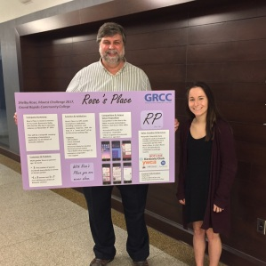 Felix Pereiro stands next to Shelby Rose. He holds her posterboard presentation for the Rose's Place app. They stand near the Meijer Business Center in the Main Building.