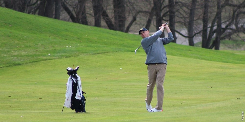 A GRCC golfer swings his club. His bag is on a stand near him.